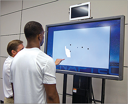 A demonstration prepares an athlete for multiple object tracking on Senaptec Sensory Station.