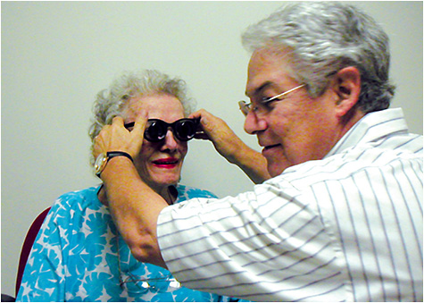 Dr. Shuldiner assists a patient with her low vision aid.
